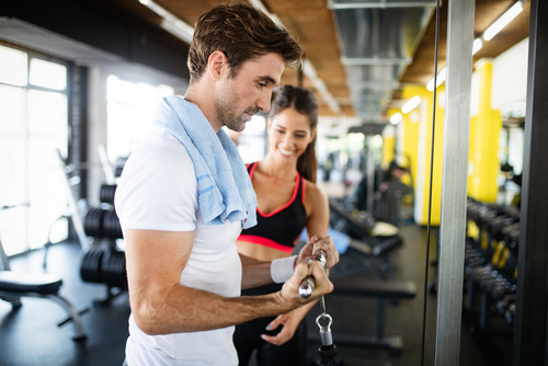 FIt happy woman personal trainer helping man in gym